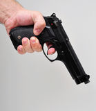 Hand holding a pistol. Isolated on grey background royalty free stock images