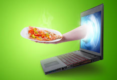 Hand holding a pizza slice coming out of a laptop screen Stock Images
