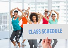 Hand holding placard with class schedule text against women dancing in background stock image