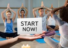 Hand holding placard that reads start now against people doing meditation Stock Image