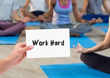 Hand holding placard that reads work hard against people doing meditation Stock Image