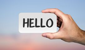 Hand holding placard with word HELLO. Communication concept. royalty free stock photos
