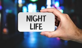 Hand holding placard with word NIGHT LIFE. stock photos