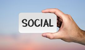 Hand holding placard with word SOCIAL. Communication concept. stock images
