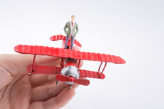 Hand holding plane with a figure on it Stock Photos