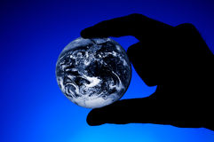 Hand holding planet Earth. Silhouette of a hand holding planet Earth over blue background Stock Photos