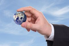 Hand holding planet earth. Caucasian hand holding a small earth with a blue sky background Stock Photos