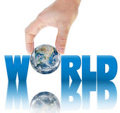 Hand holding planet Earth on a background of the inscription WORLD. Stock Photography