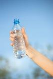 Hand holding plasic bottle of water. Hand holding plastic bottle of water in front of sky Stock Photography