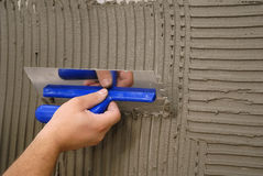 Hand holding plastering tool Royalty Free Stock Images
