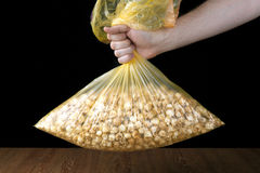Hand holding a plastic bag of popcorn. On a black background stock photography
