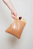 Hand holding plastic bag with tap full of apple juice Royalty Free Stock Images