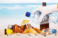 Hand holding  plastic bottle on  pile  garbage in  sand background. Stock Photo