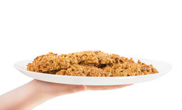 Hand holding plate with oatmeal biscuits. Royalty Free Stock Photos