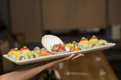 Hand holding plate with sushi. Royalty Free Stock Photos