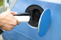 Hand holding plug for Charging  electric car Royalty Free Stock Images