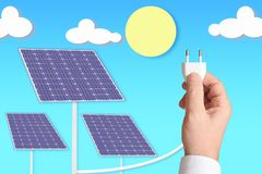 A hand holding a plug connected to some solar photovoltaic panels. Renewable energy concept Royalty Free Stock Images