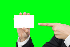 Hand holding and pointing blank business card. For copyspace isolated on green background with clipping path Stock Photography
