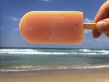 Hand holding popsicle horizontally above the sea Royalty Free Stock Photo