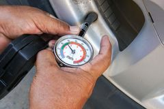 Hand holding pressure gauge for car tire pressure measurement. Vehicle safe concept Royalty Free Stock Photo