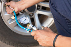 Hand holding pressure gauge for car tyre  measurement Royalty Free Stock Image