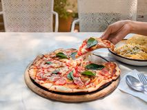 Hand is holding and pulling a slice of pizza margherita out of the tray royalty free stock images