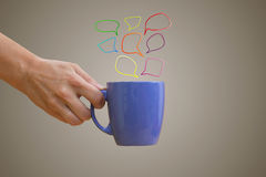 Hand holding purple mug with hand-drawn multicolored speech bubb Royalty Free Stock Photos