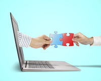Hand holding puzzle coming out from screen connect with another Royalty Free Stock Images