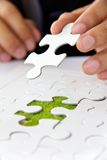 Hand holding a puzzle piece, green space concept Stock Images