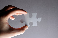 Hand holding a puzzle piece Stock Photos