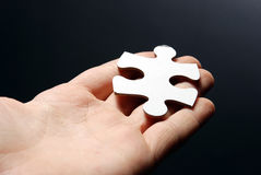 Hand holding a puzzle piece Stock Photo