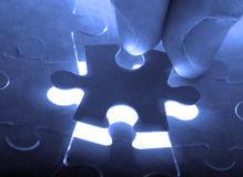 Hand holding puzzle piece close up Stock Photos