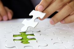 Hand holding a puzzle piece Royalty Free Stock Images