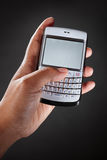 Hand holding qwerty handphone Royalty Free Stock Image