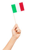 Hand holding and raising small paper Italian flag. Woman`s hand holding and raising small paper Italian flag, isolated on white Stock Photography