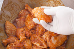 Hand holding raw chicken wings in spice prepare for cooking Stock Images