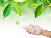 Hand holding, receiving or giving bottle of water. with green leaf background Stock Photo