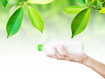 Hand holding, receiving or giving bottle of water, with green leaf background Royalty Free Stock Image