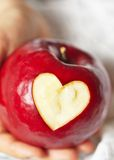 Hand holding red apple with heart Royalty Free Stock Images