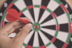 Hand holding red arrow target center of dartboard. Concept business goal to marketing success Royalty Free Stock Image