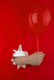 Hand holding red balloon. Hand protruding through hole holding balloon, red background Stock Image
