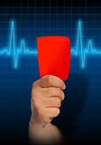 Hand holding red card on heart rate monitor Stock Image