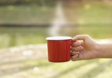 Hand holding red coffee cup in blur green gardent Stock Photo