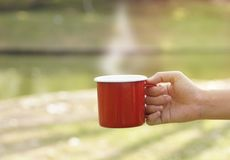 Hand holding red coffee cup in blur green Stock Photos