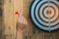 Hand holding red dart arrow ready to hitting in the target. Dartboard on wooden Royalty Free Stock Images
