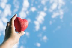 Hand holding the red decorative heart against the blue sky stock photography