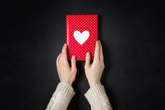 Hand holding red gift  on black. Hand holding red gift  with heart  on black Royalty Free Stock Photo