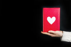 Hand holding red gift isolated on black. Background Royalty Free Stock Image