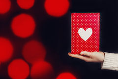 Hand holding red gift isolated on black. Background Royalty Free Stock Photo