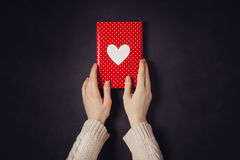 Hand holding red gift isolated on black. Hand holding red gift with heart isolated on black Royalty Free Stock Photography